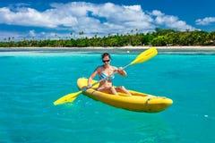 Mulher que Kayaking no oceano em férias na ilha de Fiji tropical Fotos de Stock