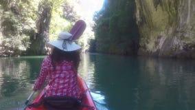 Mulher que kayaking no ponto de vista bonito da parte traseira da parte traseira da câmera da ação da lagoa da menina que rema no filme