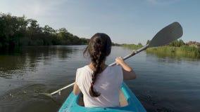 Mulher que kayaking no rio em um dia ensolarado filme