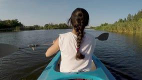 Mulher que kayaking no rio em um dia ensolarado video estoque