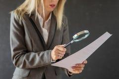 Mulher que lê com cuidado o contrato do negócio com lupa imagens de stock