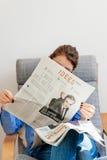 Mulher que lê Le Monde sobre cândido presidencial de Francois Fillon Imagem de Stock Royalty Free