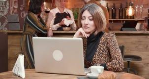 Mulher que lê muito cuidadoso e focalizada uma mensagem importante em seu portátil vídeos de arquivo