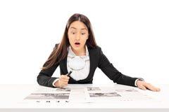 Mulher que lê a notícia através de uma lupa Fotografia de Stock