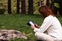Mulher que lê o livro digital Imagem de Stock Royalty Free