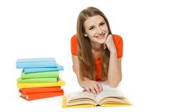 Mulher que lê o livro que encontra-se no assoalho fotografia de stock