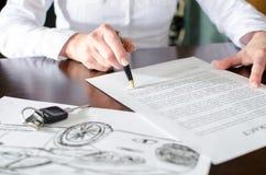 Mulher que lê um contrato de compra do carro Fotos de Stock Royalty Free