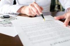 Mulher que lê um contrato de compra do carro Imagens de Stock