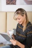 Mulher que lê um eBook em um restaurante Fotos de Stock Royalty Free
