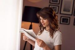 Mulher que lê um jornal imagem de stock