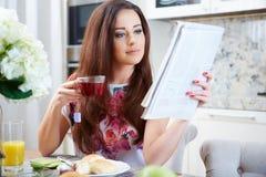 Mulher que lê um jornal fotografia de stock