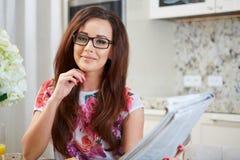 Mulher que lê um jornal foto de stock