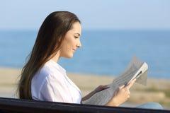 Mulher que lê um jornal fora na praia fotografia de stock royalty free