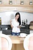 Mulher que lê um livro de cozinha Fotografia de Stock Royalty Free