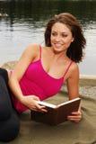 Mulher que lê um livro em um lago Foto de Stock Royalty Free
