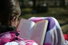 Mulher que lê um livro exterior Imagens de Stock Royalty Free