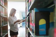 Mulher que lê um livro na biblioteca Retrato do readin da universitária fotos de stock