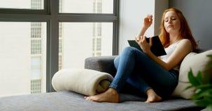 Mulher que lê um livro na sala de visitas 4k video estoque