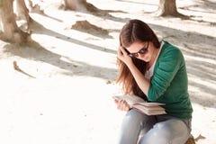 Mulher que lê um livro no parque imagem de stock