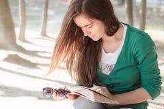 Mulher que lê um livro no parque perto do lago imagens de stock royalty free