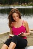 Mulher que lê um livro por um lago Fotografia de Stock