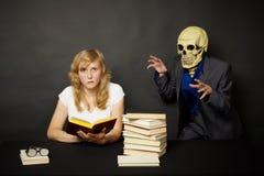 Mulher que lê um livro terrível na obscuridade Fotos de Stock Royalty Free
