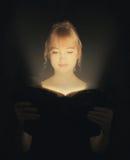 Mulher que lê uma Bíblia de incandescência. foto de stock