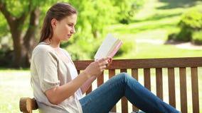 Mulher que lê uma novela ao sentar-se em um banco vídeos de arquivo