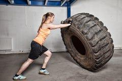 Mulher que lança o crossfit do pneu Foto de Stock