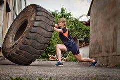 Mulher que lança um treinamento do crossfit do pneu Imagem de Stock