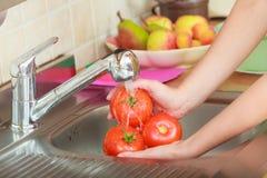 Mulher que lava legumes frescos na cozinha Fotografia de Stock Royalty Free
