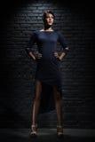 Mulher que levanta ao lado da parede Imagens de Stock