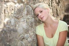 Mulher que levanta contra a parede de pedra Fotografia de Stock Royalty Free