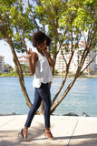 Mulher que levanta em calças de brim magros e em estiletes que acenam ao afro-americano do afro da câmera Imagens de Stock