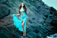 Mulher que levanta em uma praia com rochas fotografia de stock royalty free
