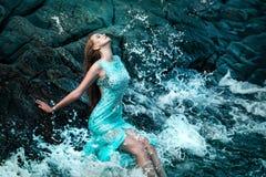 Mulher que levanta em uma praia com rochas Imagens de Stock