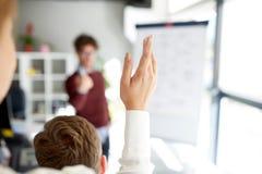 Mulher que levanta a mão na apresentação no escritório fotografia de stock