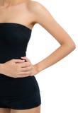 Mulher que levanta o corpo saudável bonito e que faz massagens sua cintura na área da dor Imagem de Stock