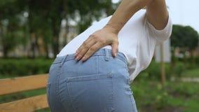 Mulher que levanta-se dor nas costas de sentimento do banco da mais baixa, raizes de nervo comprimidas video estoque