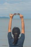 Mulher que levanta-se na praia e na mão com mostrar óculos de sol imagem de stock royalty free