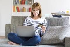 Mulher que limpa a conta bancária de seu marido com o cartão de crédito fotografia de stock royalty free