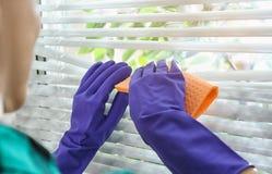 Mulher que limpa cortinas de janela com o pano dentro Antes e depois da limpeza imagens de stock