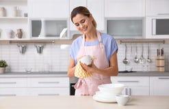 Mulher que limpa o copo cerâmico na tabela com os pratos limpos imagens de stock royalty free