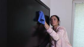 Mulher que limpa para fora a tevê do tela plano filme