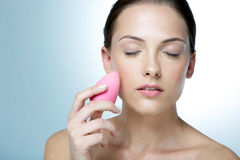 Mulher que limpa sua cara com os olhos fechados Fotos de Stock