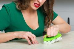 Mulher que limpa sua cozinha Fotografia de Stock Royalty Free