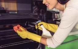 Mulher que limpa sua cozinha fotos de stock