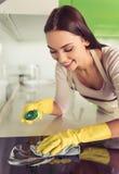 Mulher que limpa sua cozinha imagem de stock