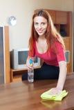 Mulher que limpa a tabela de madeira com o pano e o limpador Imagem de Stock