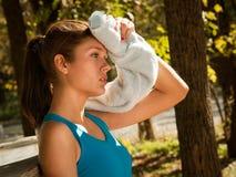 Mulher que limpa a testa com a toalha Imagem de Stock Royalty Free